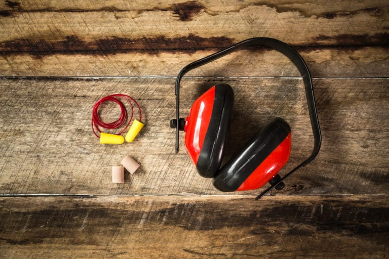 Earplugs and Ear Protection laid out on a wooden style background