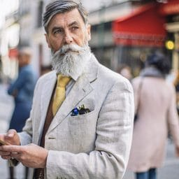 Older gentleman with a single hearing aid holding a cellphone