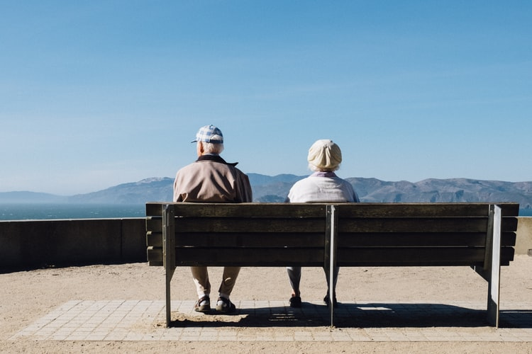Two seniors sitting on a bench