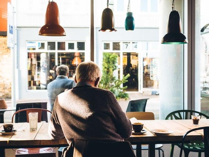 Man sits inside of a coffee shop