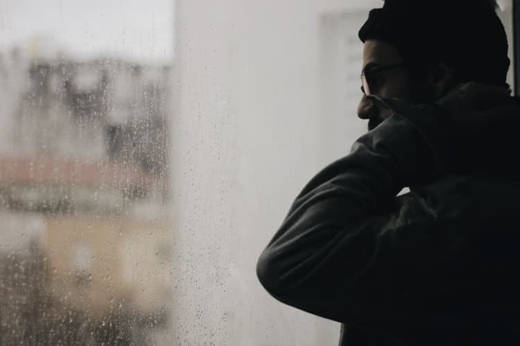 Man looking outside rainy window.