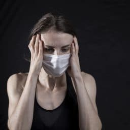 Woman in a mask with a headache.